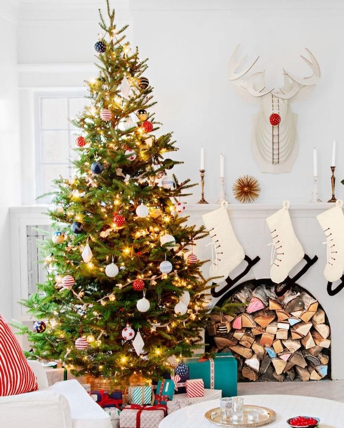 decoration sapin de noel traditionnel en guirlandes lumineuses, boules de noel bleues, blanches et rouges, cheminée blanche avec bois, pied de sapin de paquets cadeaux colorés, deco murale rudolphe en papier