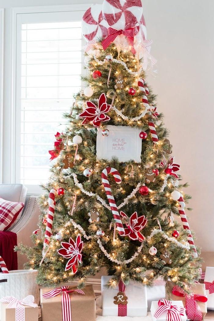 deco sapin de noel en rouge et blanc, cannes de sucre décoratif, etoiles de noel en rouge et blanc, guirlande lumineuse et pic de sucettes rouge et blanc