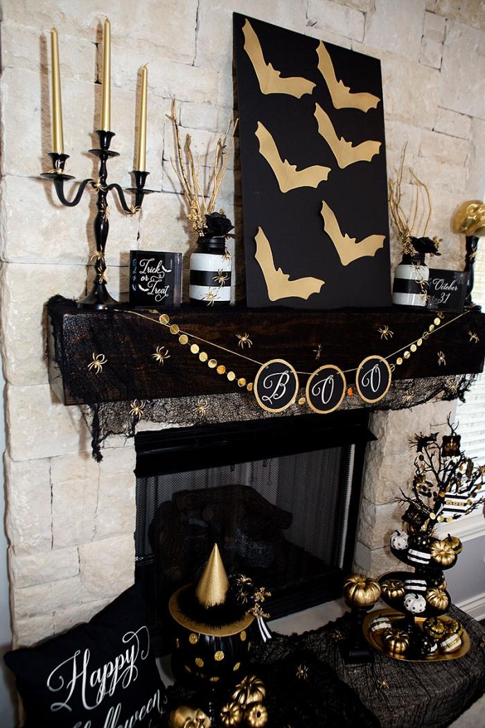 decoration d interieur, salon aux murs en pierre beiges avec cheminée noire décorée en guirlande et objets noir et or pour Halloween