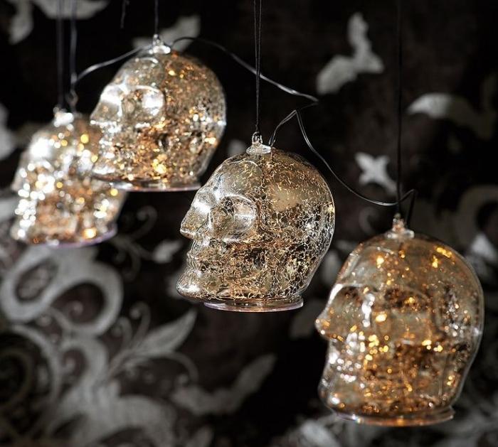 soiree halloween, chambre aux murs noirs avec déco à motifs volutes gris et guirlande lumineuse Halloween à motifs crânes dorés