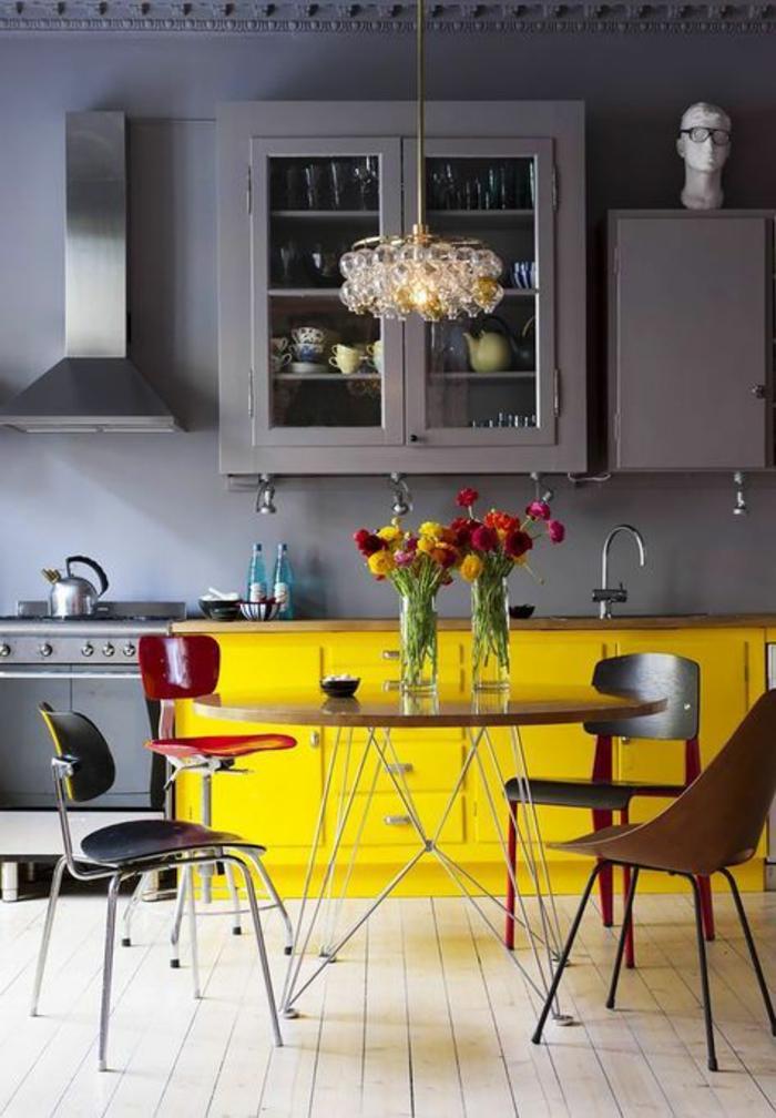 cuisine bleu canard, peinture bleu canard, quatre chaises de couleurs diverses autour de la table, sol en parquet beige, frises néo-classiques au plafond