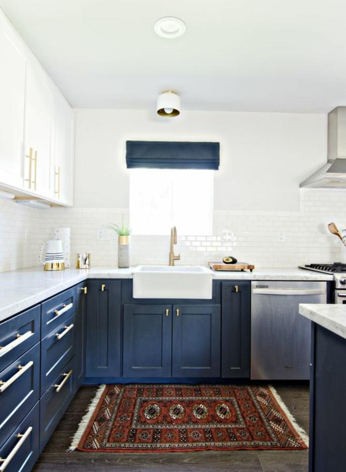 meuble bleu canard, cuisine avec des murs blancs, sol au carrelage en couleur taupe, tapis en couleurs brique, blanc et noir, aspirateur inox, îlot en bleu canard et blanc