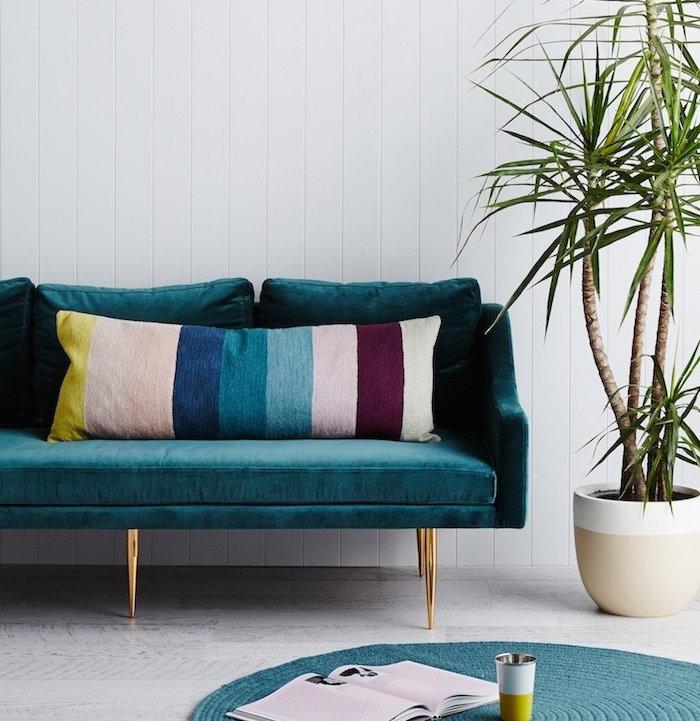 canapé bleu pétrole, coussins à rayures rose, rouge, bleu et jaune, plante verte, revêtement sol blanc, tapis rond bleu canard, mur en lambris blanc