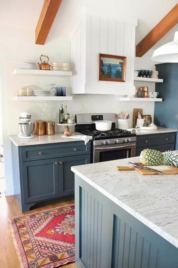 cuisine bleu avec des poutres en marron clair sur le plafond en blanc, tapis coloré avec des franges blanches, plans de travail des meubles aux effets marbrés, parquet poli beige