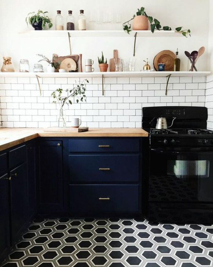 cuisine bleu, carrelage en gris t noir, crédence en briques blanches,étagère blanche avec des verres et des plats, fourneaux en noir