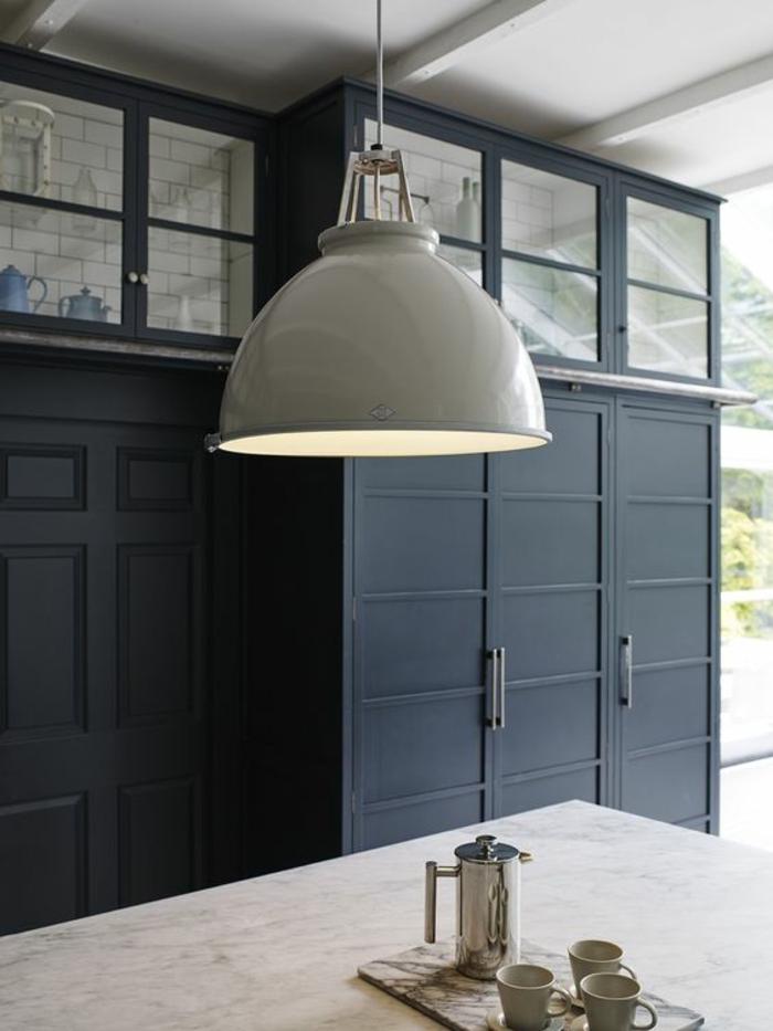 cuisine bleu canard, luminaire en style industriel en gris clair, îlot de cuisine avec plan en revêtement imitation marbre clair, meubles de rangement hauts en bleu canard