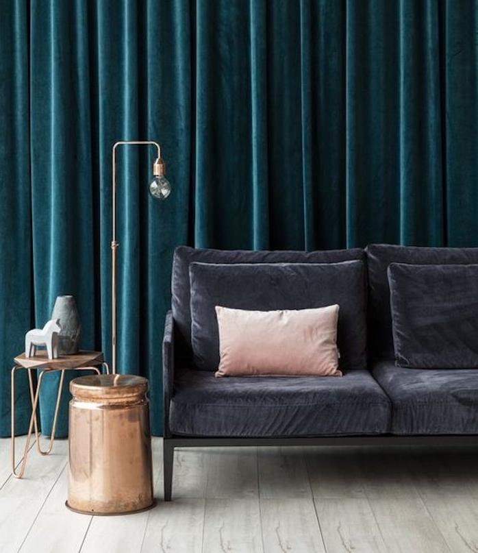 rideau bleu pétrole pour une ambaince théâtrale, canapé gris anthracite, coussin rose, parquet gris clair, table d appoint et lampe en cuivre