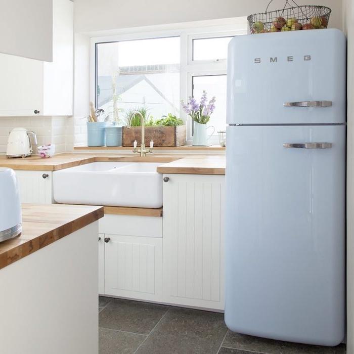 campagne decoration cuisine avec carrelage effet béton, meuble cuisine blanc, frigo bleu clair, plan de travail bois et carrelage blanc