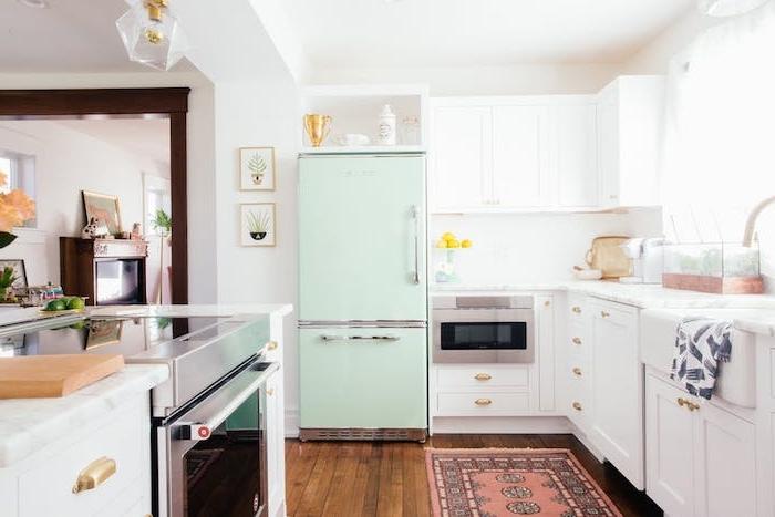 exemple de design cuisine campagnarde avec mobilier cuisine blanc, petit tapis oreintal rouge, frigo vert menthe, parquet marron et électroménager en inox