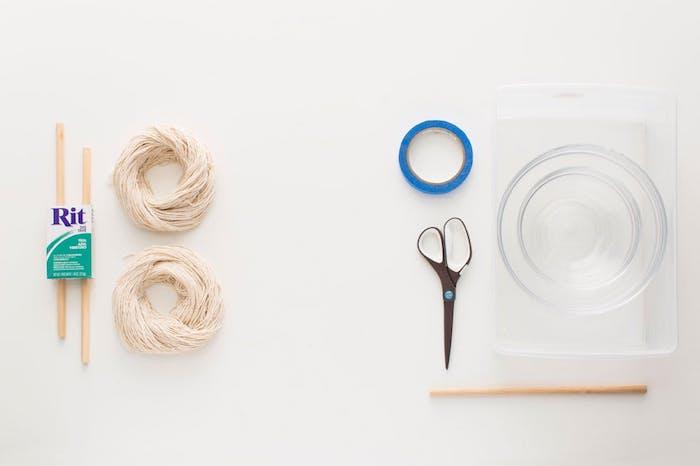 matériaux nécessaires pour fabriquer un macramé, ficelle de coton, gabuettes en bois, ciseaux, bol en verre, washi tape, colorant textile