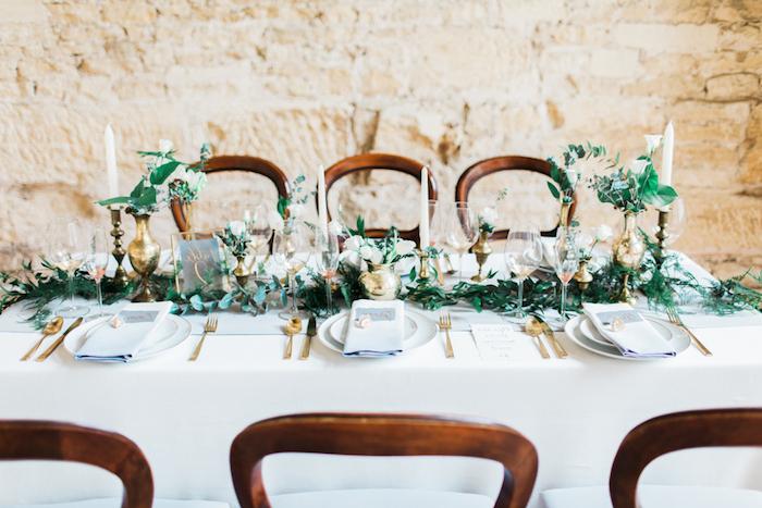 deco table mariage, nappe blanche, centre de table feuillages, fleurs dans de petits vases dorées, bougies blanches, mur de fond en pierre, réception dans une grange