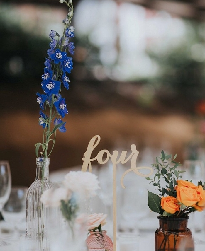 décoration champêtre, soliflores, petites bouteilles fioles avec des fleurs, visselle en verre, nappe blanche