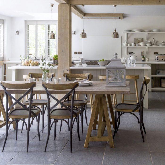 modele de deco cuisine rustique avec poutres apparentes, chaises et table en bois brut, sol dallage effet beton, ilot central gris clair et etageres blanches