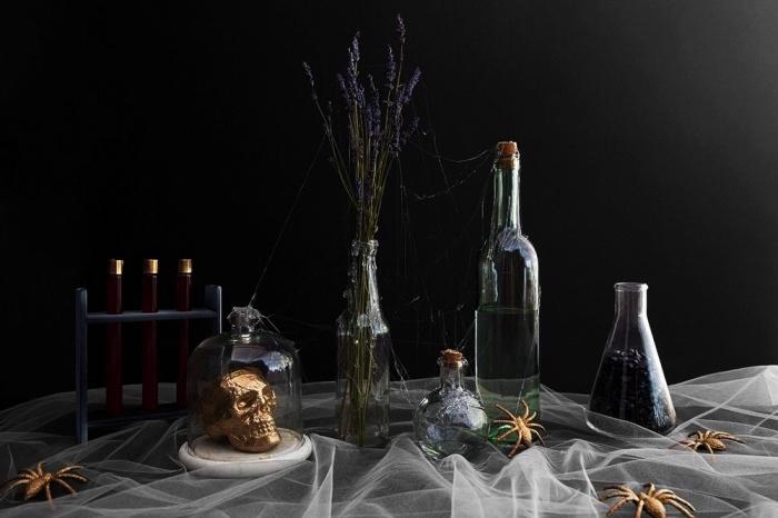 decorer sa maison, pièce aux murs noirs avec table décorée style halloween en toile d'araignée de tulle blanche et crâne en polystyrène