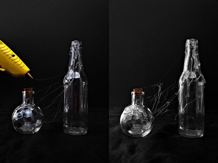 activité halloween, pistolet à colle chaude jaune pour faire toile d'araignée sur les bouteilles en verre