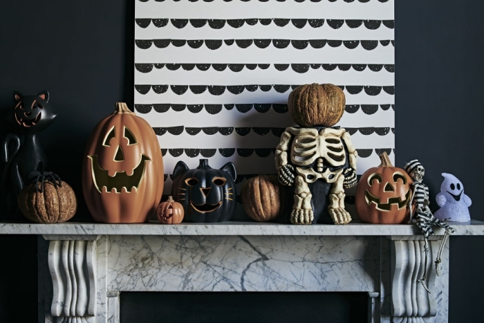 activité halloween, salon aux murs noirs avec cheminée marbre et peinture blanc et noir, figurines décoratives pour Halloween en orange et noir