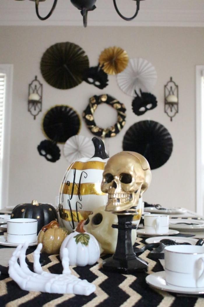 repas halloween, idée comment arranger la table Halloween en blanc noir et or, modèle de citrouille peinte en blanche avec lignes dorées