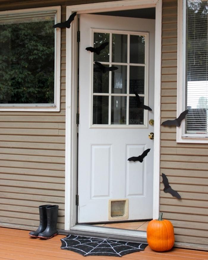 porte d'entrée blanche avec déco simple pour Halloween en chauves-souris papier noir et citrouille orange