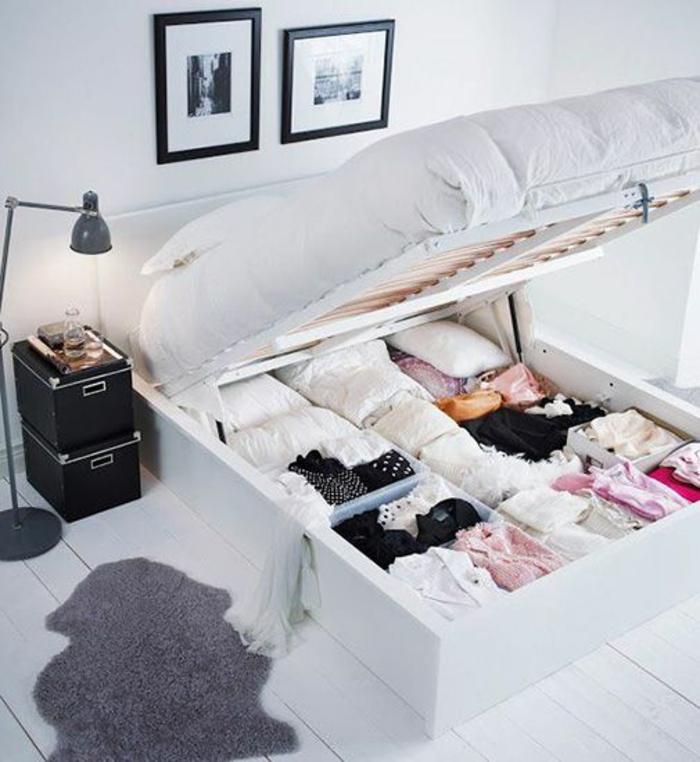 décoration chambre adulte avec grand lit qui a des espaces de rangement en dessous, sorte de garde-robe, avec deux tableaux aux cadres noirs