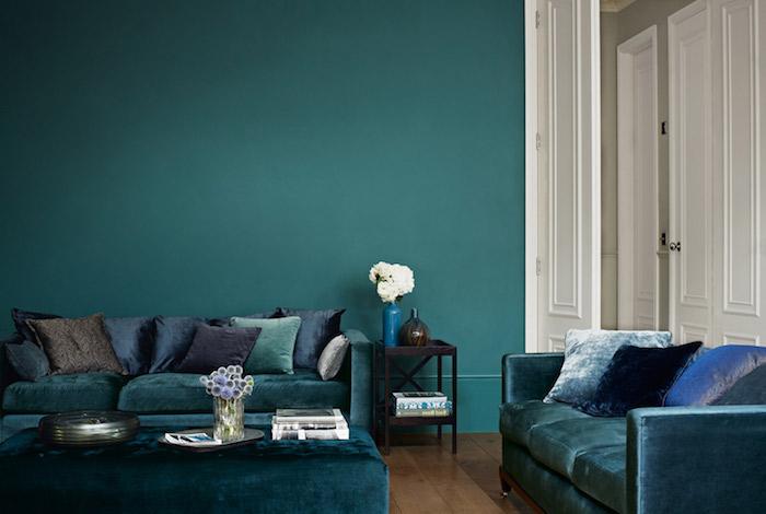 deco salon bleu canard tirant vers la couleur pétrole, parquet marron, canapés et table basse de nuance pétrole, coussins bleu, vert et gris foncé