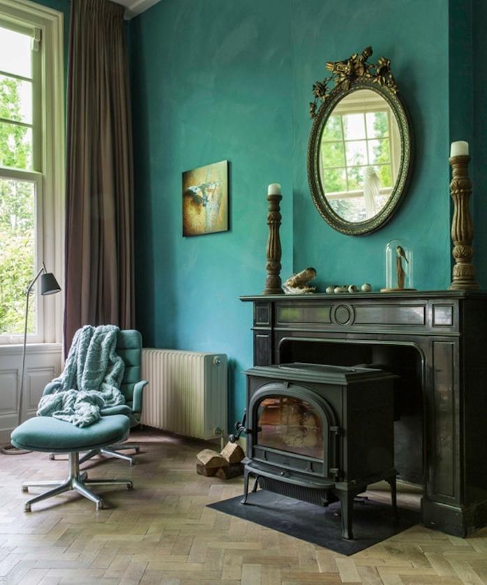 modele de deco salon bleu canard, mur couleur pétrole, cheminée noire rétro, parquet clair, chaise pivotant bleu ciel, rideau marron, miroir baroque