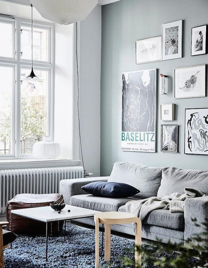 salon vert d eau, style scandinave avec des murs couleur céladon, canapé gris, deco mural de cadres avec dessins en noir et blanc, tapis gris, tabouret en bois, table basse noire avec plateau de marbre, tabouret en cuir, suspension blanche