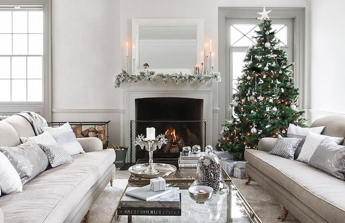 deco salon scandinave en blanc et gris, sapin de noel naturel en guirlandes lumineuses, boules et ornements argentés, pic en étoile blanche, cheminée, décoré de guirlande de pin enneigé et bougies