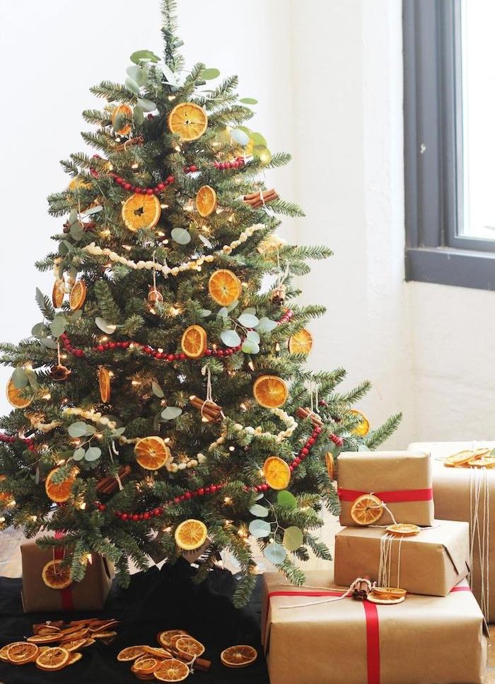 comment décorer un sapin de noel, decoration de rondelles d orange séché et batons de cannelle, guirlande de perles rouges, paquets cadeaux en papier kraft