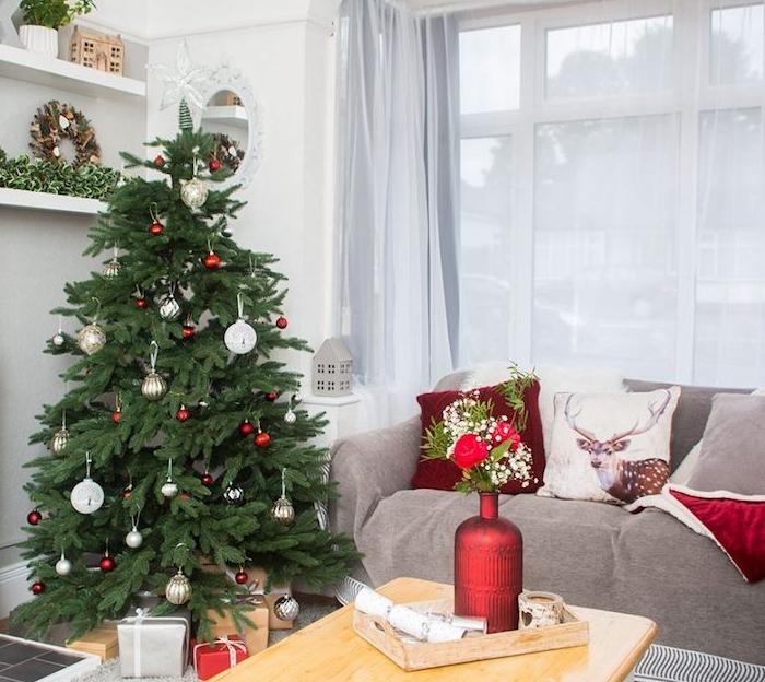 deco sapin de noel naturel avec decoration de boules de noel rouges, blanches et argent, table basse en bois, canapé gris décoré de coussins de noel