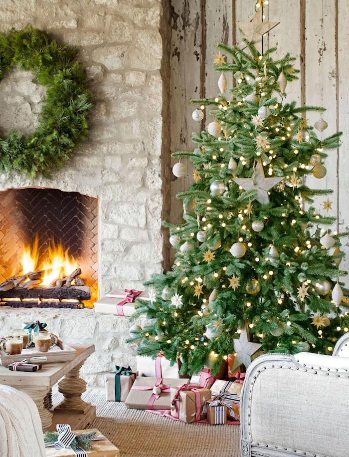 sapin de noel décoré dans un coin près d une cheminée rustique en pierre, boules de noel blanches et dorées, petites étoiles décoratives et guirlande lumineuse, paquets cadeaux avec emballage papier kraft