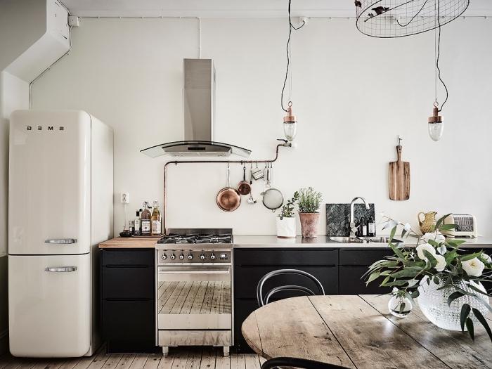 cuisine en bois, lampes suspendues avec finitions en cuivre, table ronde en bois massif avec chaises en noir