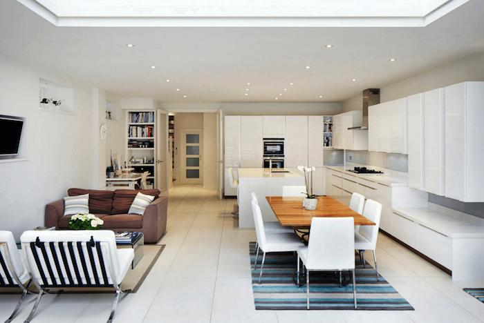 idée déco studio, comment aménager une cuisine en longueur blanche avec table en bois et chaises blanches, revetement sol blanc et tapis à rayures bleues, canapé marron et chaises blanches, coin travail au fond