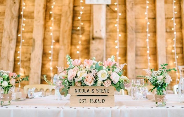exemple de deco table mariage, nappe blanche, cagette bois fleurie, que faire avec des pots en verre, vases décorés de bandes de jute et ruban, guirlandes lumineuses