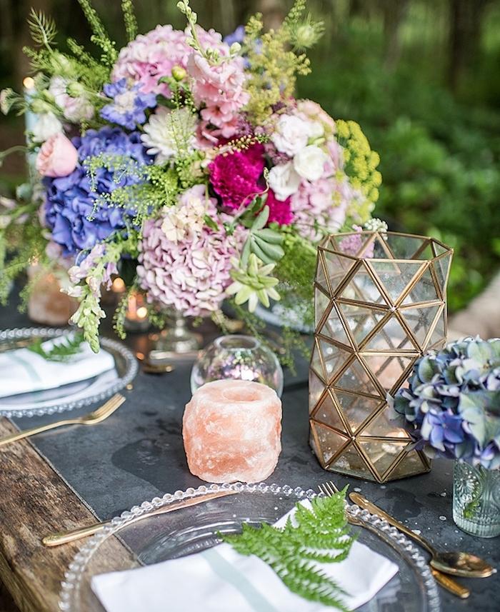 deco table mariage rustique avec des fleurs colorés, rose, fuchsia et violettes, bougies, assiettes en verre et feuille verte dans la serviette