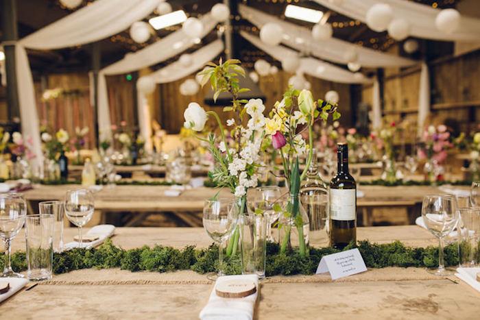 mariage champetre chic, decoration des mousse en guise de centre de table, bouteilles en verre transformés en vases, marque place originale en rondin bois avec nom invité gravé, table en bois rustique