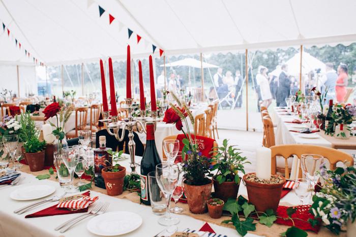 deco table mariage rouge, bougeoir avec des bougies rouges, chemin de table en jute, pots de fleurs, lierre, guirlande fanions