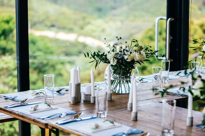 deco mariage champetre, tables en bois rustiques, bougeoirs beton avec des bougies blanches, roses dans des vases boules