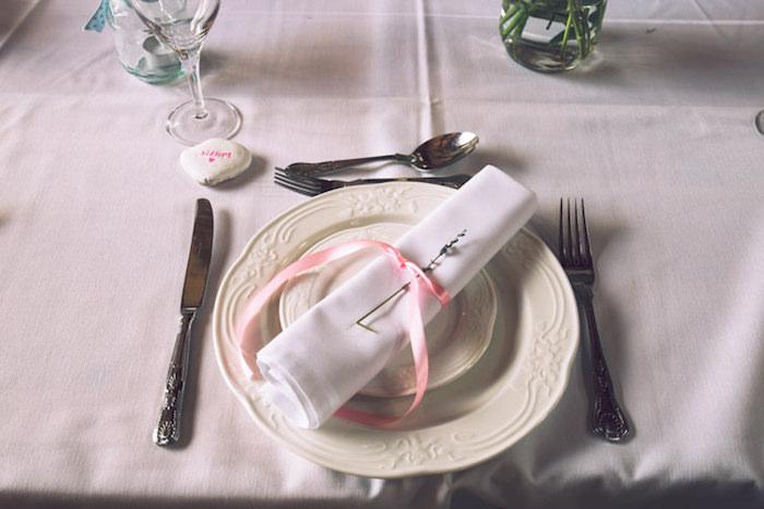 idée de deco table mariage, couverts argentés sur une nappe blanche, serviette blanche, décoré de ruban rose et brin de lavande
