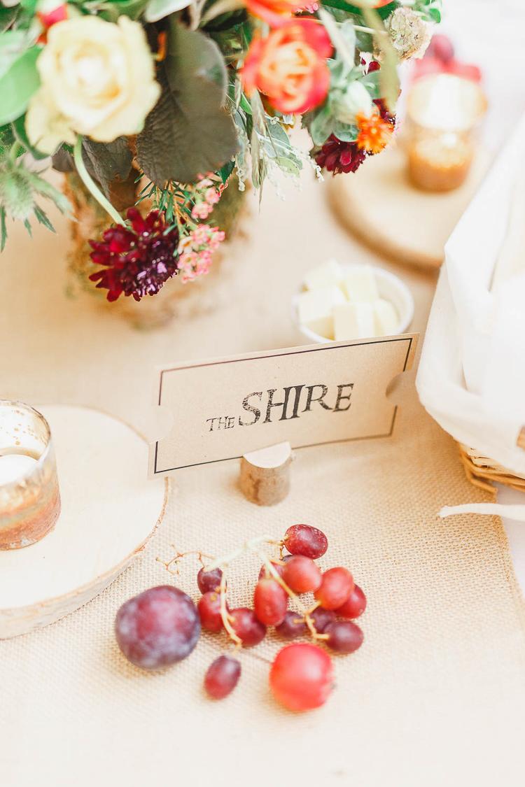 deco table mariage, nappe en toile de jute, nom invité inséré dans une branche en bois, decoration florale et fruits, bougeoirs diy mariage