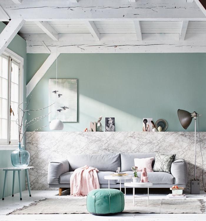 salon vert d eau, teinte celadon, avec pan de mur effet marbre gris, canapé gris perle, pouf vert, coussin et couverture rose, lampe grise, poutres apparentes blanches, tables basses blanches