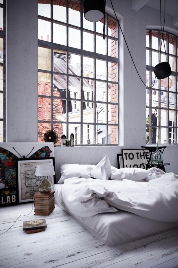 lit industriel bas avec oreillers blancs, peinture à design papillon et poster mots inspirants, chambre loft aux murs blancs