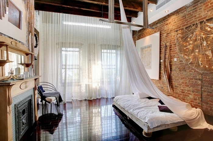 intérieur de chambre à coucher à design loft industriel aux murs en briques et plafond en poutres marron foncé