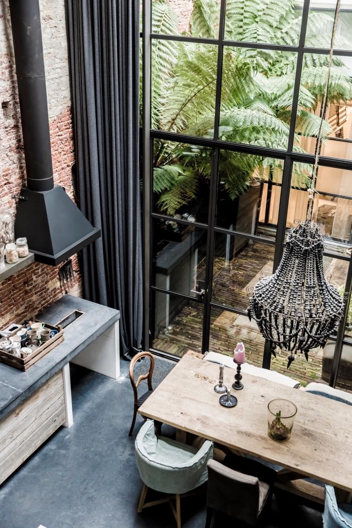 meuble style industriel, grandes fenêtres surdimensionnées avec rideaux longs en gris anthracite, cuisine ouverte avec salle à manger intégrée