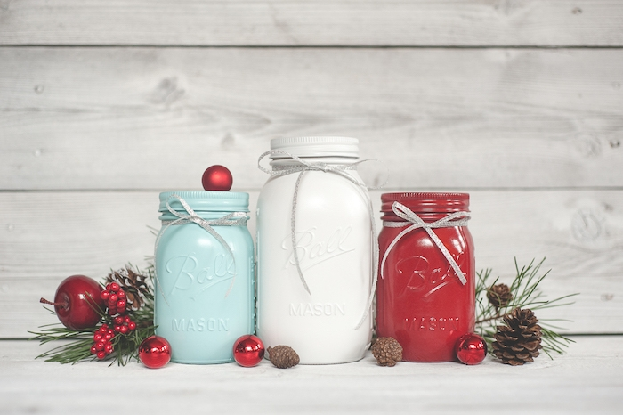 idée de decoration de noel a faire soi meme de pots en verre repeints de couleur bleue, rouge et blanche, pommes de pin et boules de noel rouges, branches de pin