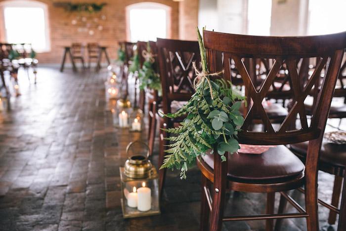 decoration mariage champetre pour la salle de mariage, mur en pierre, lanternes avec des bougies, chaises en bois fleuris