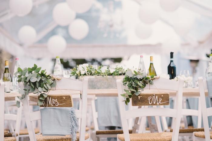 deco champetre pour votre mariage, table et chaises blanches fleuris, décorées de feuillages, centre de table floral, ballons blancs
