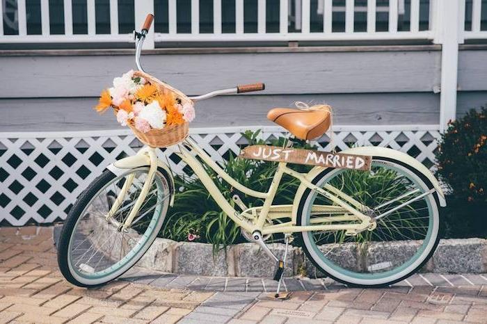 bouquet champetre dans un panier accroché au guidon d un velo, tout juste marié écrit sur une planche en bois