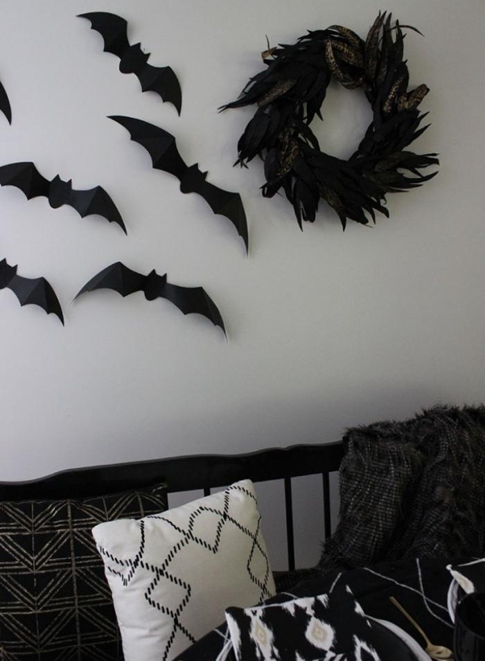 decorer sa maison pour la fête Halloween, salon aux murs blancs avec déco en papier chauves-souris noirs