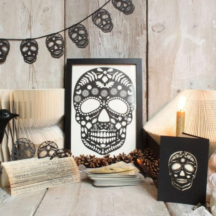 bricolage halloween, guirlande diy en crânes noirs de papier, cadre photo décoratif en noir avec peinture noir et blanc
