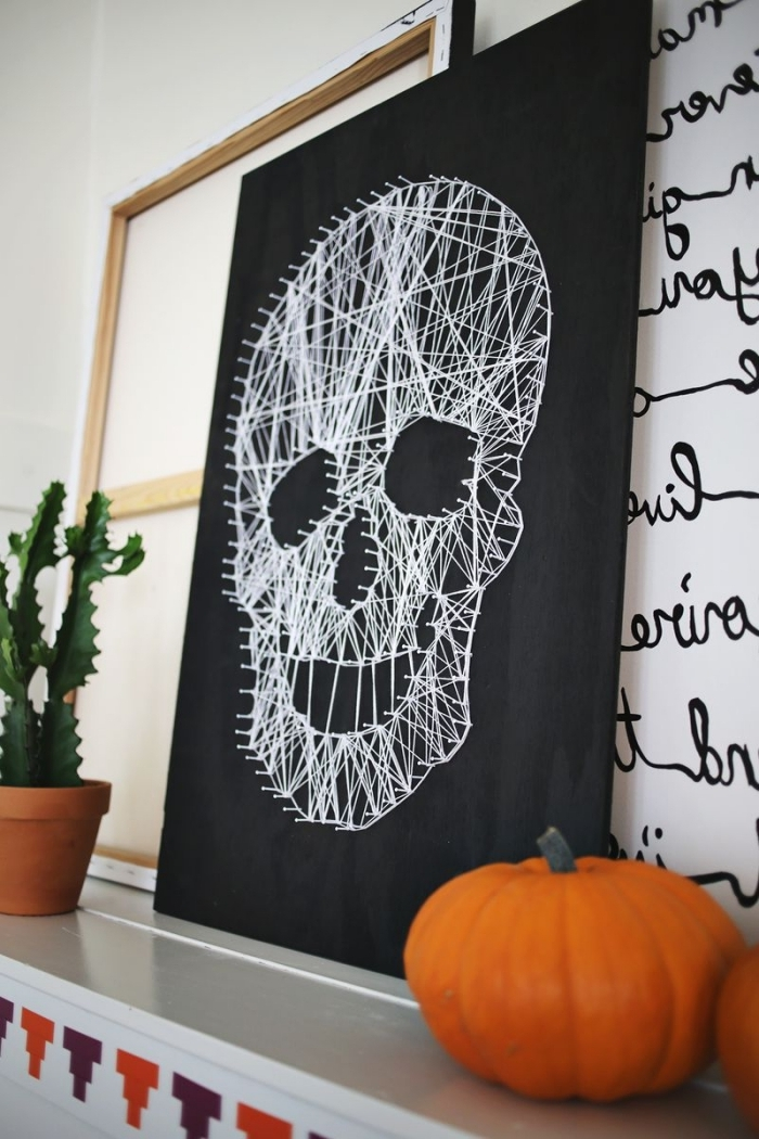 objets décoratif pour Halloween, peinture noire avec crâne en fils blancs, cadre photo bois peint en blanc et noir